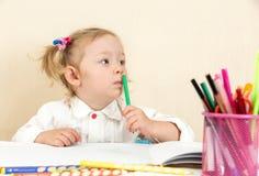 Милый чертеж девушки ребенка с красочными карандашами и ручка войлок-подсказки на таблице в детском саде Стоковая Фотография RF