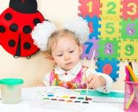 Милый чертеж девушки ребенка с красочными карандашами и ручка войлок-подсказки в preschool в детском саде Стоковое Фото
