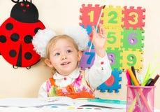 Милый чертеж девушки ребенка с красочными карандашами и ручка войлок-подсказки в preschool в детском саде Стоковые Изображения RF