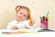 Милый чертеж девушки ребенка с красочными карандашами и ручка войлок-подсказки в preschool в детском саде Стоковое фото RF