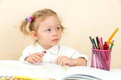 Милый чертеж девушки ребенка с красочными карандашами и ручка войлок-подсказки на таблице в детском саде Стоковые Изображения