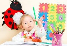 Милый чертеж девушки ребенка с красочными карандашами на таблице в детском саде Стоковые Фото