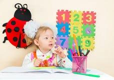 Милый чертеж девушки ребенка с красочными карандашами на таблице в детском саде Стоковые Фотографии RF