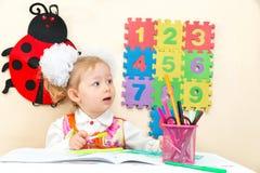 Милый чертеж девушки ребенка с красочными карандашами на таблице в детском саде Стоковое Изображение RF
