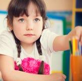 Милый чертеж девушки с красочными карандашами на детском саде Стоковая Фотография