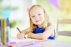 Милый чертеж маленькой девочки с красочными карандашами на daycare Творческая картина ребенк на школе стоковое изображение