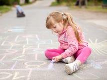 Милый чертеж маленькой девочки с мелом outdoors Стоковые Фото