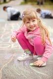 Милый чертеж маленькой девочки с мелом outdoors Стоковое Фото