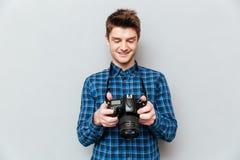 Милый человек смотря изображения на его камере стоковое изображение