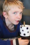 Милый школьник выпивает milkshake Стоковое фото RF