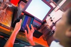 Милый barmaid используя сенсорный экран пашет Стоковые Фото