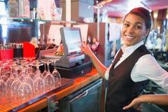 Милый barmaid используя сенсорный экран пашет Стоковая Фотография