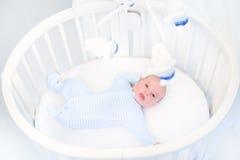 Милый newborn ребёнок в игрушках круглой шпаргалки наблюдая Стоковая Фотография