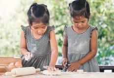 2 милых азиатских девушки маленьких ребенка подготавливают тесто для печь Стоковые Изображения