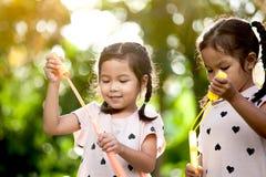 2 милых азиатских девушки ребенка имея потеху, который нужно сыграть с пузырями Стоковые Фото