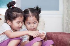 2 милых азиатских девушки ребенка имея потеху для того чтобы сыграть игру в smartphone Стоковое Изображение RF
