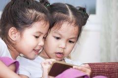 2 милых азиатских девушки ребенка имея потеху для того чтобы сыграть игру в smartphone Стоковая Фотография RF
