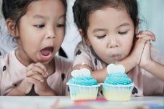 2 милых азиатских девушки ребенка дуя пирожное дня рождения Стоковые Фотографии RF