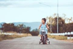 2 милых азиатских девушки ребенк имея потеху для того чтобы ехать велосипед совместно Стоковые Изображения