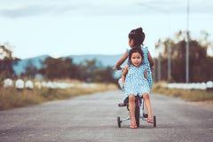 2 милых азиатских девушки ребенк имея потеху для того чтобы ехать велосипед совместно Стоковые Изображения RF
