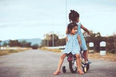 2 милых азиатских девушки ребенк имея потеху для того чтобы ехать велосипед совместно Стоковые Фото