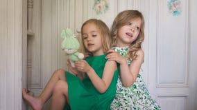 2 милых белокурых девушки в платьях обнимая один другого и усмехаться акции видеоматериалы
