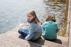 2 милых белокурых девушки сидя на озер-береге Стоковое Изображение RF