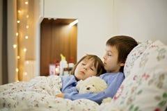 2 милых больных дет, мальчики, оставаясь в кровати с лихорадкой Стоковая Фотография