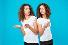 2 милых близнеца девушек смотря телефоны над голубой предпосылкой Стоковая Фотография