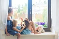 2 милых европейских девушки малыша сидя на силле около окна Стоковая Фотография RF