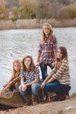 4 милых девушки в джинсах усмехаясь около реки дальше Стоковое Изображение RF