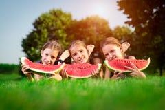 3 милых девушки есть арбуз Стоковая Фотография