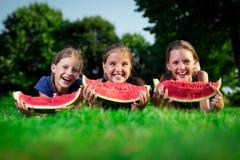 3 милых девушки есть арбуз Стоковые Изображения