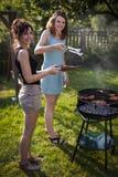 2 милых девушки делая еду Стоковые Фото