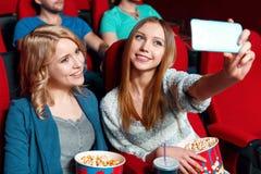 2 милых девушки делая selsie в кино Стоковое Фото