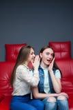 2 милых девушки злословя на красном кожаном кресле Стоковые Фото