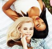 2 милых девушки на усмехаться травы счастливый, лучшие други имея потеху совместно, концепция людей образа жизни Стоковая Фотография RF