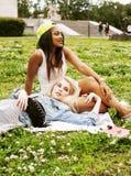 2 милых девушки на усмехаться травы счастливый, лучшие други школы имея потеху совместно, концепция людей образа жизни Стоковое Изображение RF