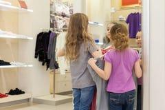 2 милых девушки около зеркала пробуют дальше одежды в современном магазине Стоковое Изображение RF