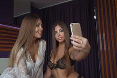 2 милых девушки принимая selfie с мобильным телефоном, девушками имея портрет года сбора винограда студии потехи Стоковые Изображения RF
