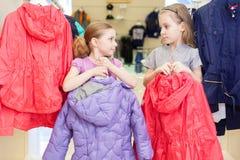 2 милых девушки пробуют дальше одежды в одеждах детей магазина Стоковые Изображения RF