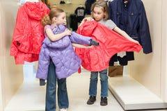 2 милых девушки пробуют дальше одежды в современном магазине Стоковое фото RF