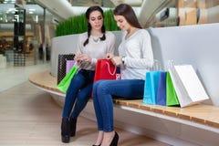 2 милых девушки сидят на стенде в моле при сумки подарка смотря внутрь Стоковое фото RF