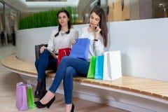 2 милых девушки сидят на стенде в моле при сумки подарка смотря внутрь Стоковые Фотографии RF
