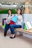 2 милых девушки сидят на стенде в моле с сумками подарка Стоковое Изображение