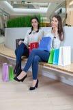 2 милых девушки сидят на стенде в моле с сумками подарка Стоковые Фотографии RF