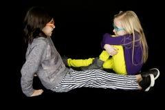2 милых девушки сидя говоря друзья нося в стиле фанк стекла Стоковые Фотографии RF