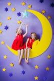 2 милых девушки сидя на большой луне Стоковое фото RF