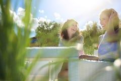 2 милых девушки сидя на смеяться над таблицы кафа Стоковая Фотография RF