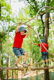 2 милых дет, братья мальчика, взбираясь в спортивной площадке s веревочки Стоковые Фотографии RF